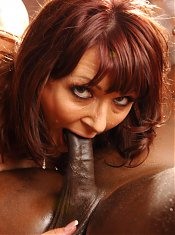 Busty redhead MILF Desi Foxx invites a black guy over and welcomes him with a blowjob